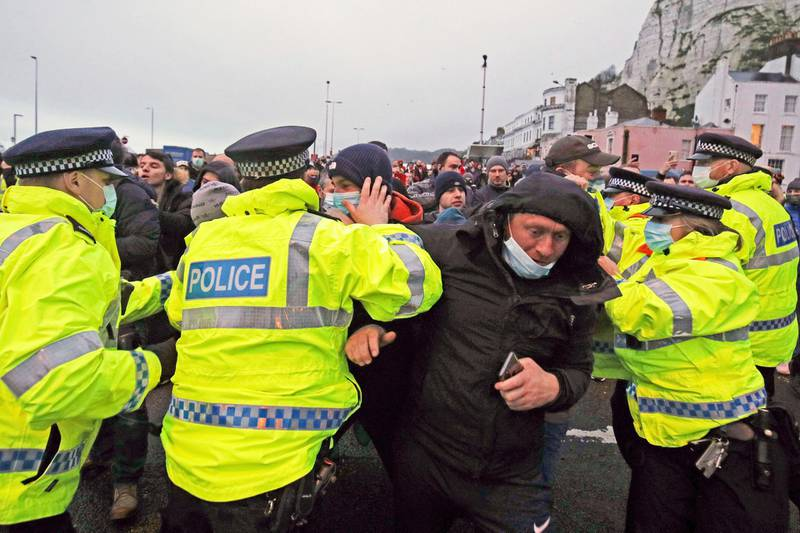 Truck drivers argue with police holding them back at the entrance to the Port of Dover, in Kent, England, Wednesday Dec. 23, 2020. Freight from Britain and passengers with a negative virus test began arriving on French shores Wednesday, after France relaxed a two-day blockade over a new virus variant that had isolated Britain, stranded thousands of drivers and raised fears of shortages. (Steve Parsons/PA via AP)