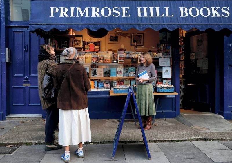 """Jessica Graham (R), owner of independent book shop Primrose Hill Books, talks to members of the public outside her shop in west London on November 6, 2020. - Some 250 small independent bookshops have joined forces to compete with online giants such as Amazon during the second coronavirus lockdown in England. Unlike other countries such as Belgium, sales of books are not deemed to be essential, despite studies indicating more people turned to reading in the first lockdown earlier this year, and outlets have had to close their doors until December 2. Bookshop.org, which was launched in the United States earlier this year, is now available in Britain and in just a few days has generated £60,000 for the retailers taking part in its """"click and collect"""" service. (Photo by Hollie Adams / AFP)"""