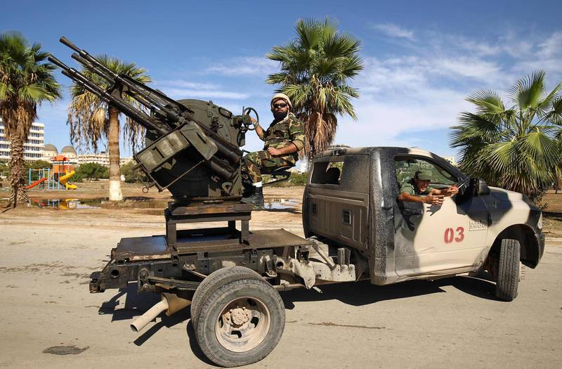Members of the Libyan security forces loyal to Libyan Strongman Khalifa Haftar man turrets mounted in the back of pickup trucks as they remain on guard duty during the 2018 edition of the Benghazi International Forum and Exhibition of Oil & Gas, in the eastern Libyan city on October 24, 2018.  / AFP / Abdullah DOMA