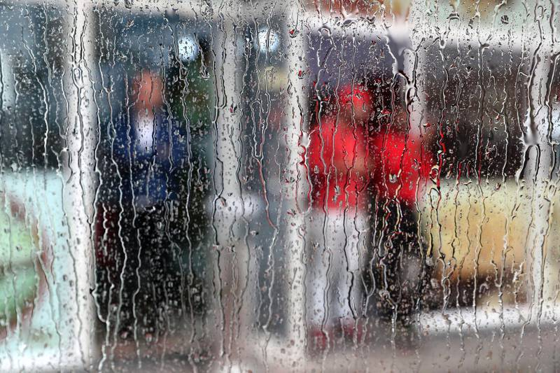 DUBAI, UNITED ARAB EMIRATES , March 22 – 2020 :- Shopkeepers outside their shops during the heavy rain in Al Barsha in Dubai. (Pawan Singh / The National) For News/Online/Instagram.