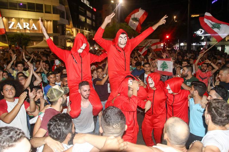 """Lebanese protesters, wearing the masks of the Spanish TV show """"La Casa de Papel"""", dance during a protest against dire economic conditions in the Lebanese southern port city of Sidon (Saida), on October 19, 2019. Tens of thousands of Lebanese people took to the streets today for a third day of protests against tax increases and alleged official corruption despite several arrests by security forces. / AFP / Mahmoud ZAYYAT"""