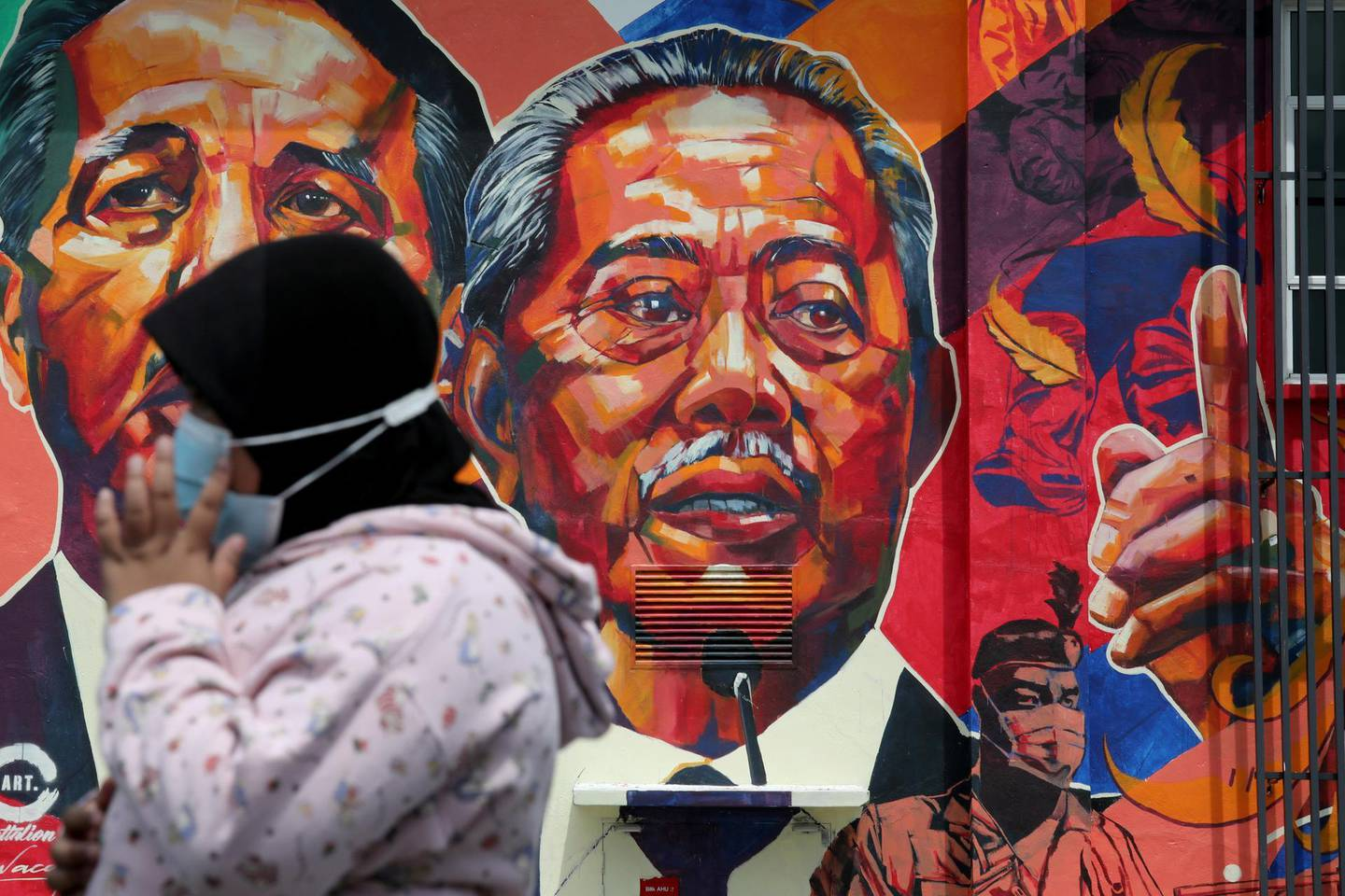 A woman passes by a mural depicting Malaysia's Prime Minister Muhyiddin Yassin in Kuala Lumpur, Malaysia October 27, 2020. REUTERS/Lim Huey Teng