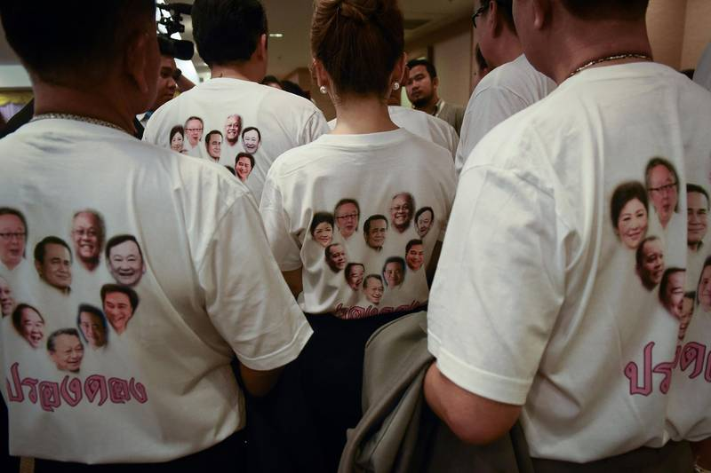 Members of the Phure Chart Thai Club wear T-shirts emblazoned with faces of political rivals, including Thailand's current Prime Minister Prayuth Chan-O-Cha  (C) and former prime ministers Thaksin Shinawatra (top R) and Yingluck Shinawatra (top L), at the Office of the Election Commission of Thailand in Bangkok on March 2, 2018. More than 30 new Thai political parties submitted names and logos on the opening day of party registration in Bangkok on March 2, an early step in the junta-ruled kingdom's halting return to democracy. / AFP PHOTO / Lillian SUWANRUMPHA