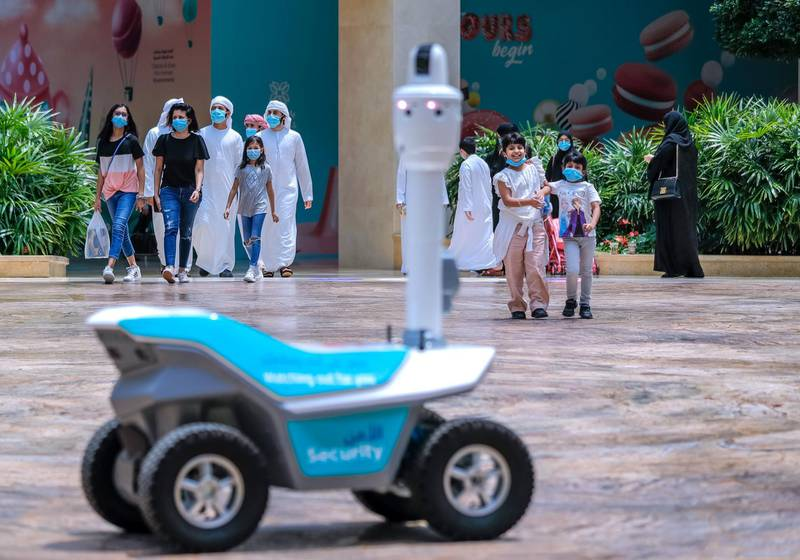 Abu Dhabi, United Arab Emirates, August 19, 2020.      Children are amazed at a roving robot on wheels which does thermal checks around the Yas Mall. Victor Besa /The National Section:  NA Reporter:  Haneen Dajani