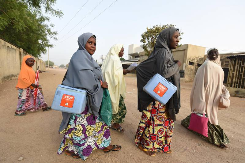 """Health workers walk from house to house in search of children to immunise during vaccination campaign against polio at Hotoro-Kudu, Nassarawa district of Kano in northwest Nigeria, on April 22, 2017. - The World Health Organization said 116 million children are to receive polio vaccines in 13 countries in west and central Africa as part of efforts to eradicate the disease on the continent. """"The synchronised vaccination campaign, one of the largest of its kind ever implemented in Africa, is part of urgent measures to permanently stop polio on the continent,"""" the WHO said. (Photo by PIUS UTOMI EKPEI / AFP)"""
