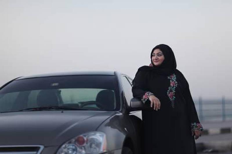 """United Arab Emirates - Ajman - November 7, 2010.  MOTORING: Shaima Al Sayed (cq-al), 34, of Ajman, poses with her 2005 Nissan Altima on the Ajman Corniche on Sunday, November 7, 2010. """"I'm so comfortable with the dimensions of this car,"""" said Al Sayed who leads a women's auto tour of the UAE every National Day. """"It's like a part of me. I never scratch or bump my car."""" Amy Leang/The National"""