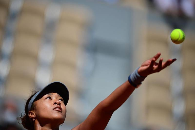 Japan's Naomi Osaka eyes the ball as she serves to Romania's Patricia Maria Tig during their women's singles first round tennis match on Day 1 of The Roland Garros 2021 French Open tennis tournament in Paris on May 30, 2021. / AFP / MARTIN BUREAU
