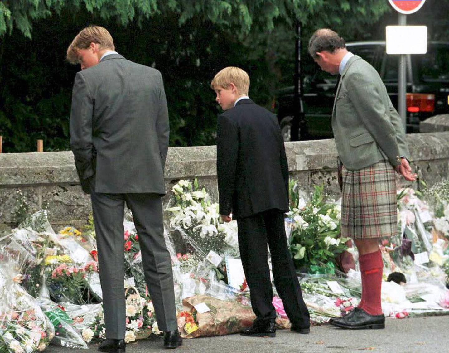 (FILES) This file photo taken on September 4, 1997 shows (L-R) Prince William, Prince Harry and their father the Prince of Wales stopping outside the gates to Balmoral Castle to look at the floral tributes.  Twenty years ago on August 31, 1997, Britain's Diana, Princess of Wales, died in a high-speed car crash in Paris. / AFP PHOTO / PRESS ASSOCIATION / CHRIS BACON