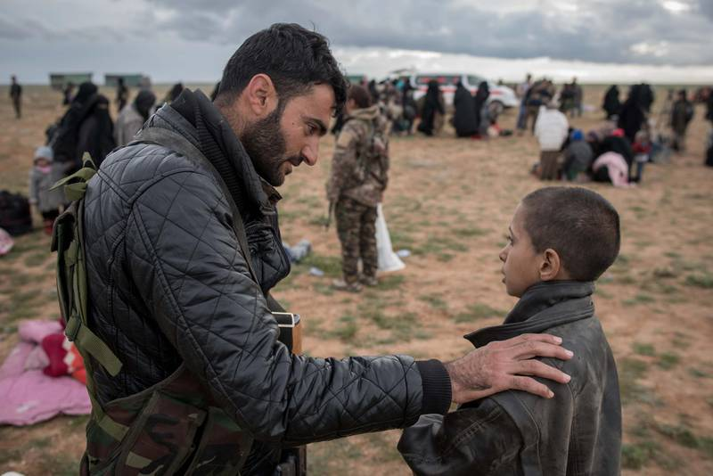 AnSDF fighter questions a young boy fleeing Baghouz. The boy said his parents had been killed. Campbell MacDiarmid