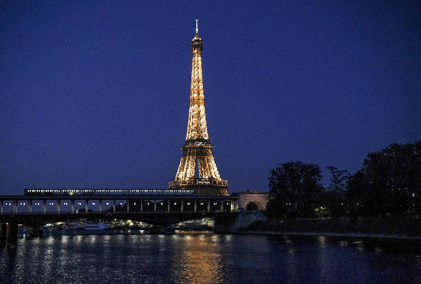 This photograph taken late April 25, 2020, shows a metro train passing along The Bir-Hakeim Bridge across The River Seine in front of The Eiffel Tower in Paris, on the 40th day of a lockdown in France aimed at curbing the spread of the COVID-19 pandemic, caused by the novel coronavirus. (Photo by ALAIN JOCARD / AFP)