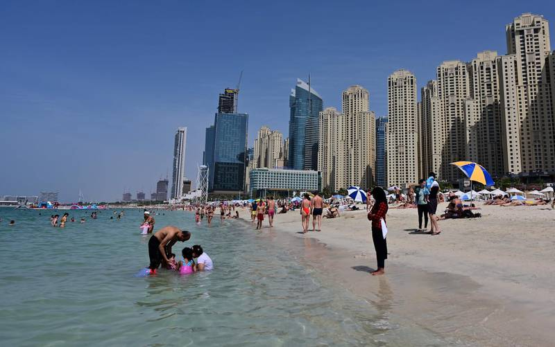 People swim in the water at Jumeirah Beach residence in Dubai on March 20, 2020 despite fears of the spread of COVID-19 coronavirus disease in the Gulf region. A series of unprecedented shutdowns to counter the fast-spreading coronavirus have impacted air travel, closing restaurants and cinemas and shutting down government and business offices in some Gulf states. / AFP / Giuseppe CACACE