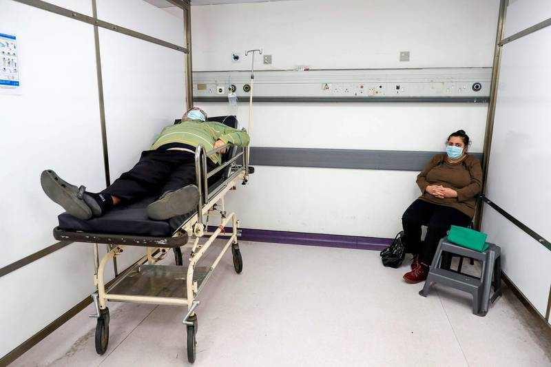 A man waits for treatment in the intensive care unit of the Rafic Hariri University Hospital in the Lebanese capital Beirut, on January 5, 2021. With 192,000 reported cases and almost 1,500 deaths, Lebanon is not among the world's worst hit countries, but its infrastructure is crumbling and a small surge in infections is enough to take its health sector to breaking point. / AFP / JOSEPH EID