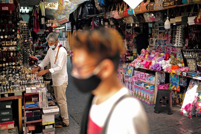 """A salesman wearing a face mask, displays his goods after opening his shop in a traditional market """"Local Souq"""", following the outbreak of the Coronavirus disease (COVID-19), in Manama, Bahrain, October 30, 2020. REUTERS/Hamad I Mohammed"""