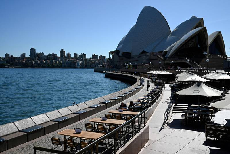 Tables at an open restaurant are seen mostly deserted on a quiet morning at the waterfront of the Sydney Opera House, where scheduled public performances have been cancelled due to the coronavirus disease (COVID-19), in Sydney, Australia, March 18, 2020.  REUTERS/Loren Elliott