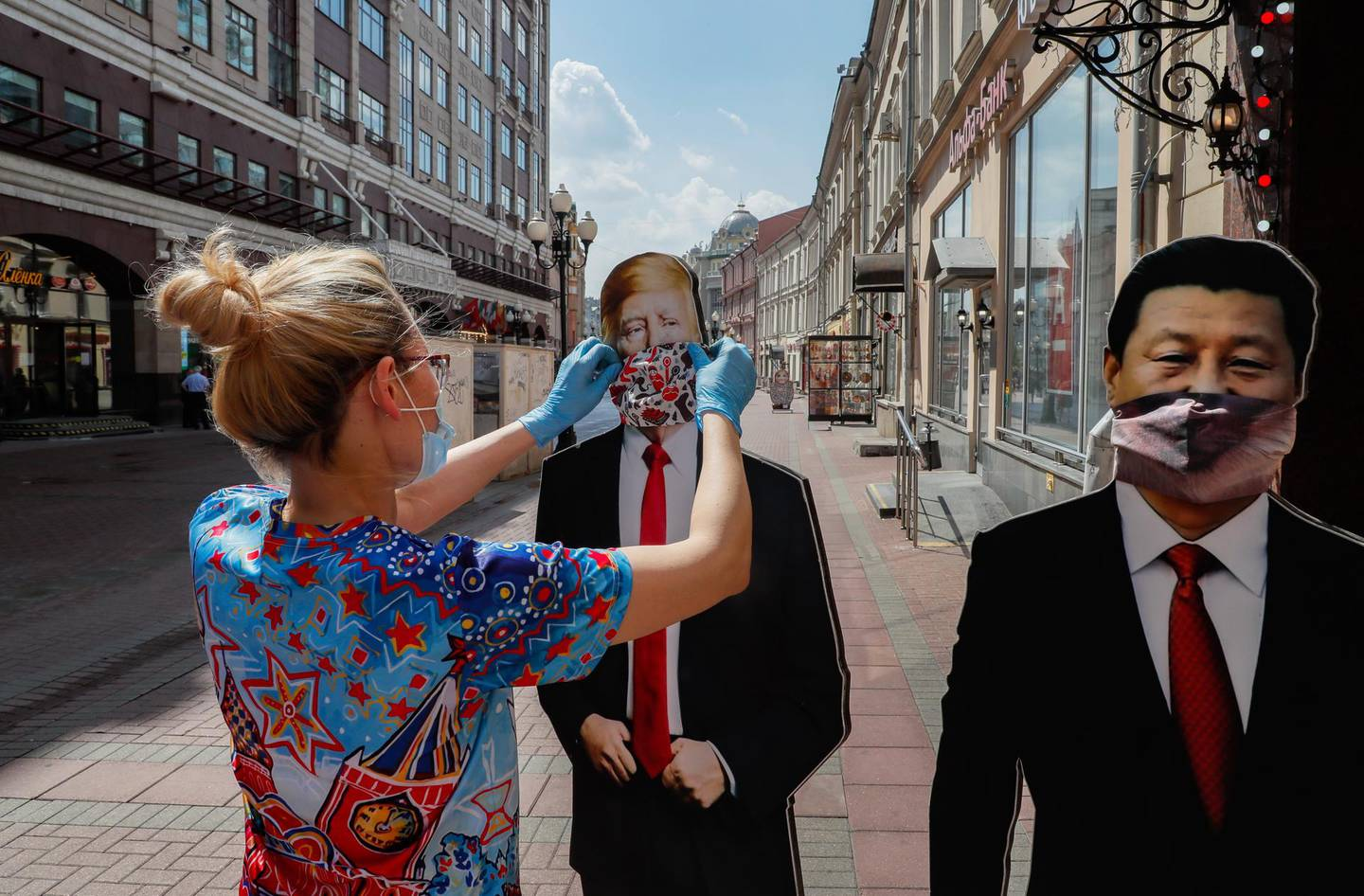 epa08472907 Gift shop salesperson sets cardboards depicting US President Donald Trump (L) and Chinese President Xi Jinping on the street after reopening the shop in Moscow, Russia, 08 June 2020. Moscow authorities have eased coronavirus restrictions. Moscow Mayor Sergei Sobyanin allowed the opening of parks and announced a resumption of work of industrial and construction enterprises.  EPA/YURI KOCHETKOV