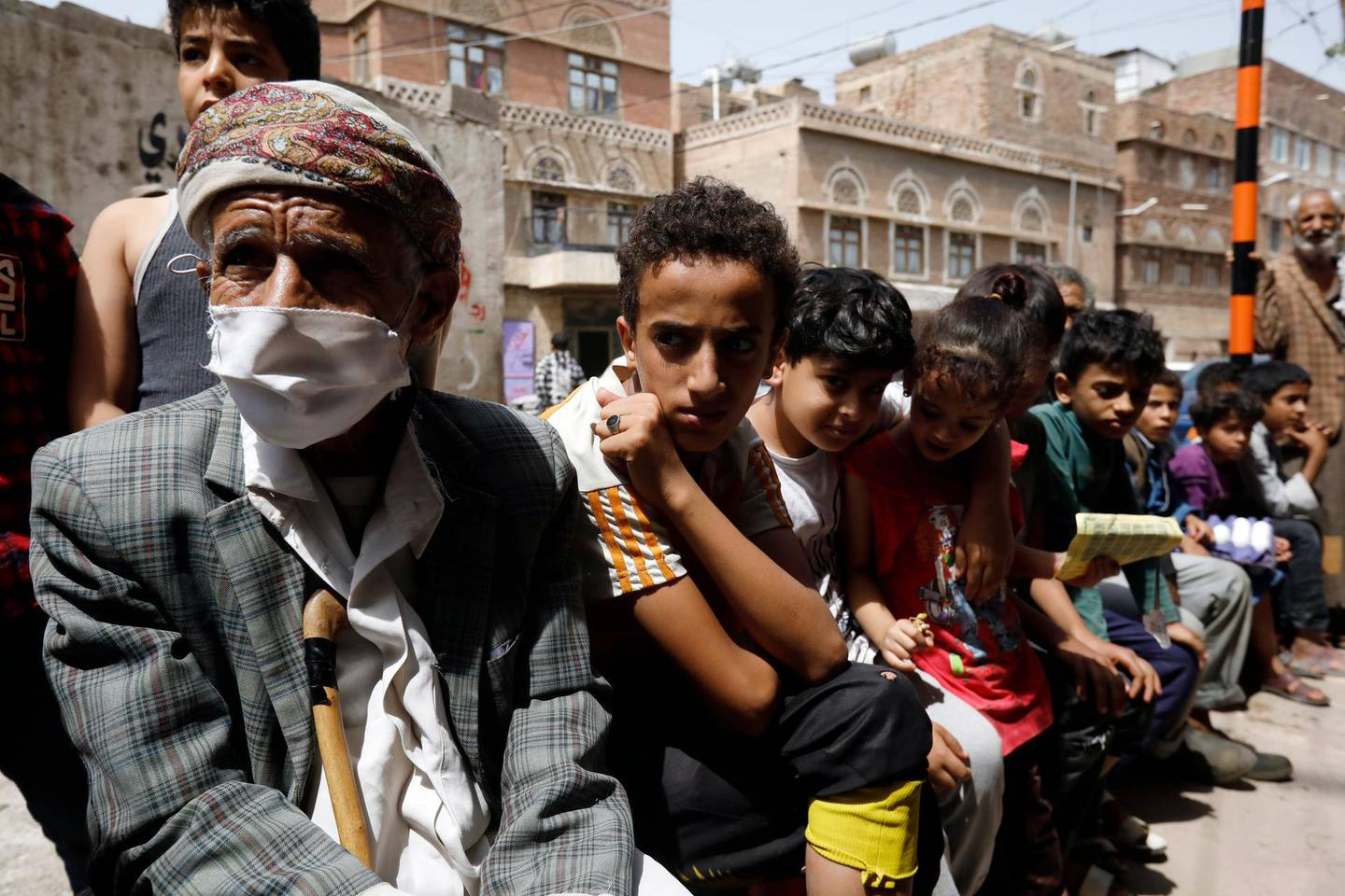 epa08537056 Yemenis wait to get free food rations from a charity group in Sana'a, Yemen, 09 July 2020. According to reports, the United Nations has warned that war-ridden Yemen is again on the brink of famine because of a lack of donor funds as 80 percent of the Arab country's 29 million-population dependent on humanitarian aid. Yemen is experiencing the world's worst humanitarian crisis, driven by more than five years of war.  EPA/YAHYA ARHAB