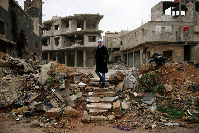 Sumaya Bairuty, 38, an English-language teacher who works in the capital Damascus, walks to her parents house in the war-damaged Bab Dreib neighborhood of Homs, Syria, Wednesday, Jan. 17, 2018.  It has been almost four years since the last remaining rebels and civilians withdrew from the remaining strongholds in the ancient heart of Homs in Syria. But few people have returned, and large parts of the once vibrant old city are still abandoned and destroyed, as if time had stood still since the guns fell silent. (AP Photo/Hassan Ammar)