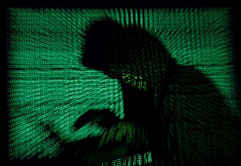 FILE PHOTO: A hooded man holds a laptop computer as cyber code is projected on him in this illustration picture taken on May 13, 2017. Top U.S. fuel pipeline operator Colonial Pipeline has shut its entire network after a cyber attack, the company said on Friday. REUTERS/Kacper Pempel/Illustration/File Photo