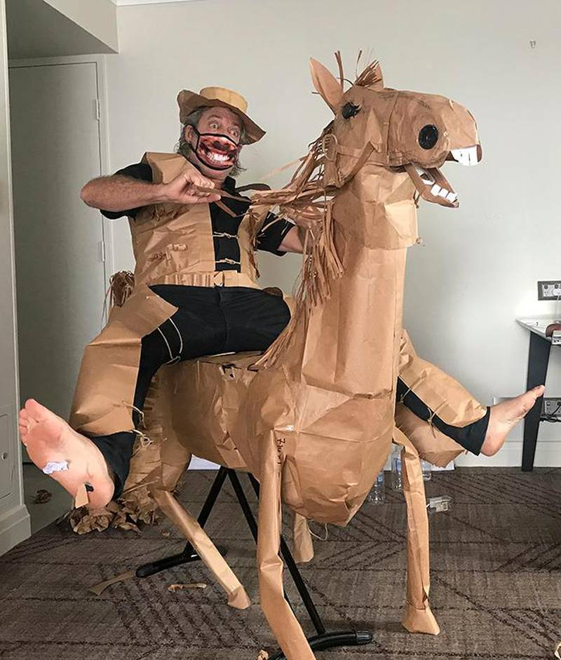 David Marriott poses with his paper horse in his hotel room in Brisbane, Australia, April 1, 2021. While in quarantine inside his Brisbane hotel room, art director Russell Brown was bored and started making a cowboy outfit from the paper bags his meals were being delivered in. His project expanded to include a horse and a clingfilm villain that he has daily adventures with, in images that have gained a huge online following. (David Marriott via AP)