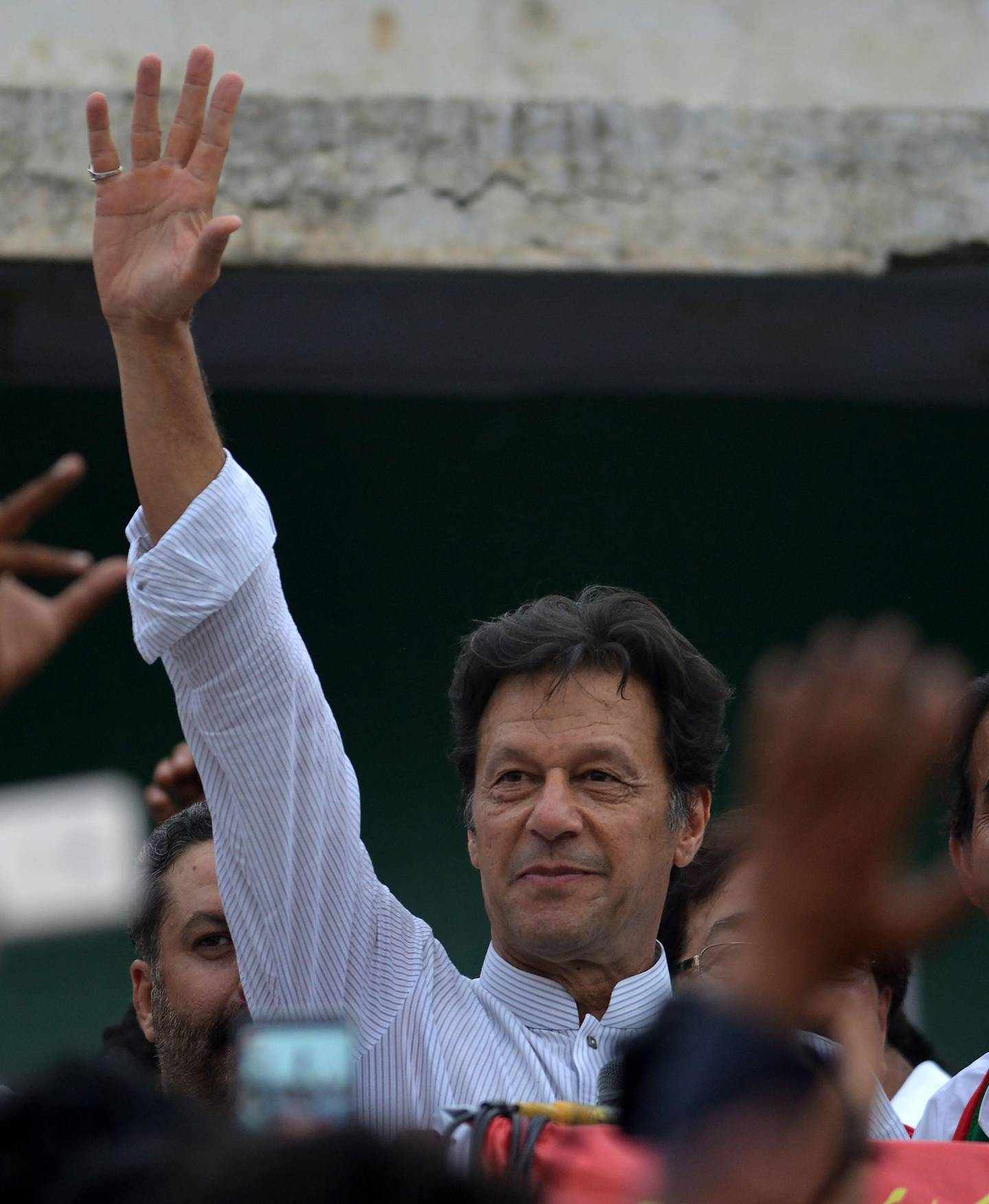 Imran Khan (C), Pakistani cricketer-turned-opposition leader and head of the Pakistan Tehreek-i-Insaf (PTI), delivers a speech during an election campaign in in Mianwali, some 240 kms southwest of Islamabad, on June 24, 2018. Pakistani cricket star-turned-politician Imran Khan on June 24 kicked off his election campaign by staging a major rally and promising sweeping changes in the country, once his party win the elections. / AFP / AAMIR QURESHI