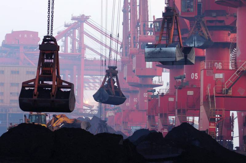 FILE - In this June 6, 2015, file photo, heavy machines move imported iron ore at the dock in Rizhao in eastern China's Shandong province.  China announced Monday, Aug. 14, 2017,  it will cut off imports of North Korean coal, iron ore and other goods in three weeks under U.N. sanctions imposed over the North's nuclear and missile programs.(Chinatopix via AP, File)
