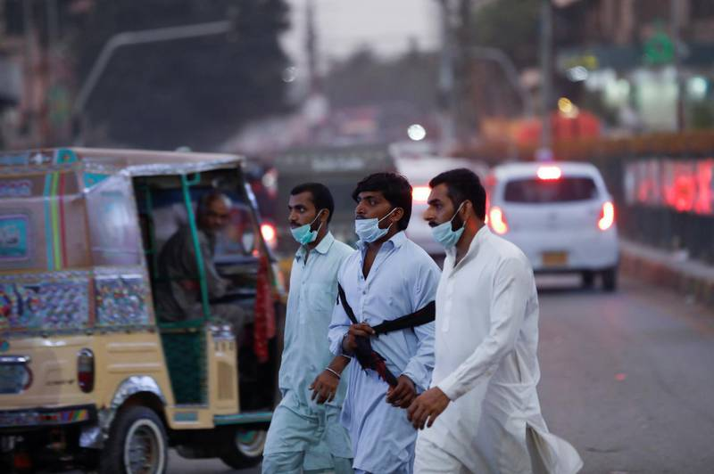 Men wearing protective masks cross a road after Pakistan lifted lockdown restrictions, as the coronavirus disease (COVID-19) outbreak continues, in Karachi, Pakistan August 18, 2020. REUTERS/Akhtar Soomro
