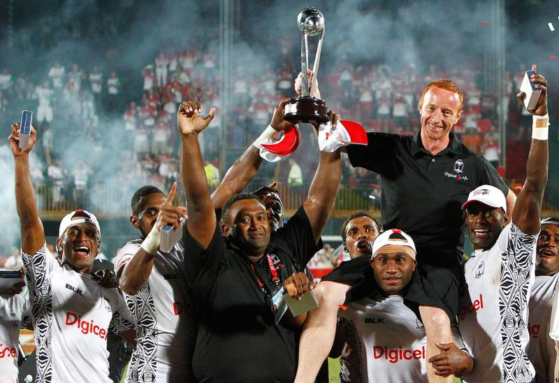 Fiji are crowned Sevens World Series Dubai Winners, while coach Ben Ryan (black shirt, red hair) celebrates with the trophy during the Dubai Rugby Sevens, at The Sevens, Dubai, on the 30th of November 2013. Credit: Jake Badger for The National *** Local Caption ***  JBadger3011_RugbySevensDay3_42.jpg
