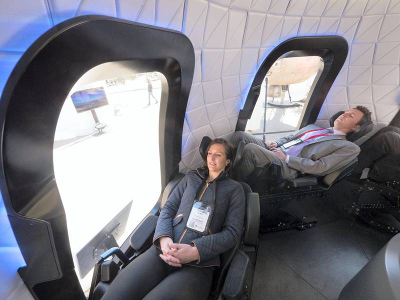 Attendees sit inside the high fidelity crew capsule mock up of the Blue Origin LLC New Shepard system during the Space Symposium in Colorado Springs, Colorado, U.S., on Wednesday, April 5, 2017. Jeff Bezos, chief executive officer of Amazon.com Inc. and founder of Blue Origin, has been reinvesting money he made at Amazon since he started his space exploration company more than a decade ago, and has plans to launch paying tourists into space within two years. Photographer: Matthew Staver/Bloomberg
