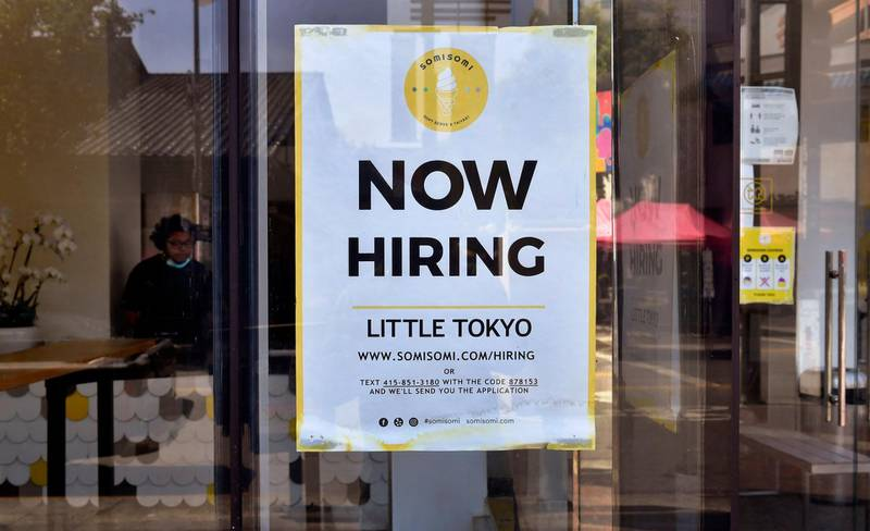 A 'Now Hiring' sign is posted in front of an ice-cream shop in Los Angeles, California on May 28, 2021.  Following over a year of restrictions due to the coronavirus pandemic, many jobs at restaurants, retail stores and bars remain unfilled, despite California's high unemployment rate, causing some owners to fear they will not be able to fully reopen by the June 15th date California has given for a full reopening of the economy. / AFP / Frederic J. BROWN