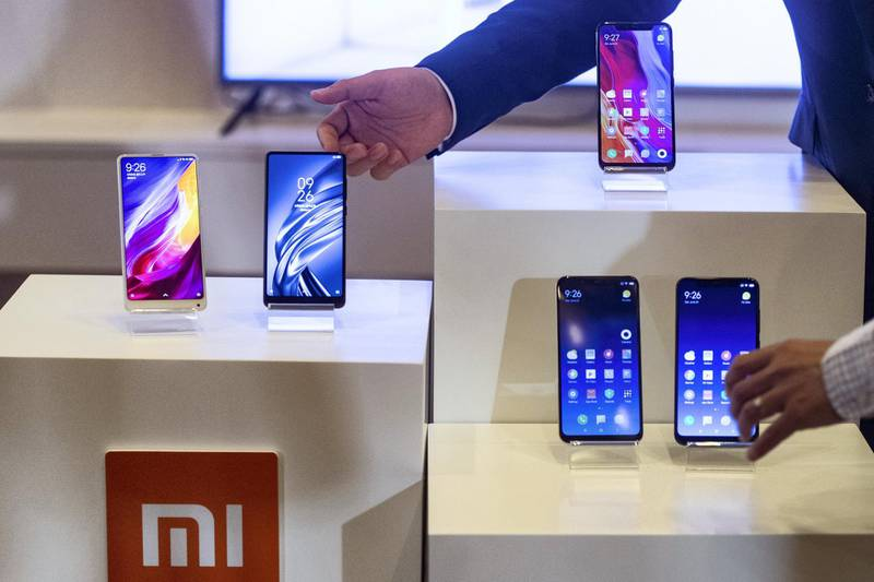 Products by Chinese smartphone maker Xiaomi are displayed during a press conference for the company's initial public offering (IPO) in Hong Kong on June 23, 2018. - Chinese smartphone maker Xiaomi kicked off its initial public offering on June 21 but the firm is likely to pull in about 6.1 billion USD, far less than originally expected, with investors having mixed views about its main business. (Photo by Philip FONG / AFP)