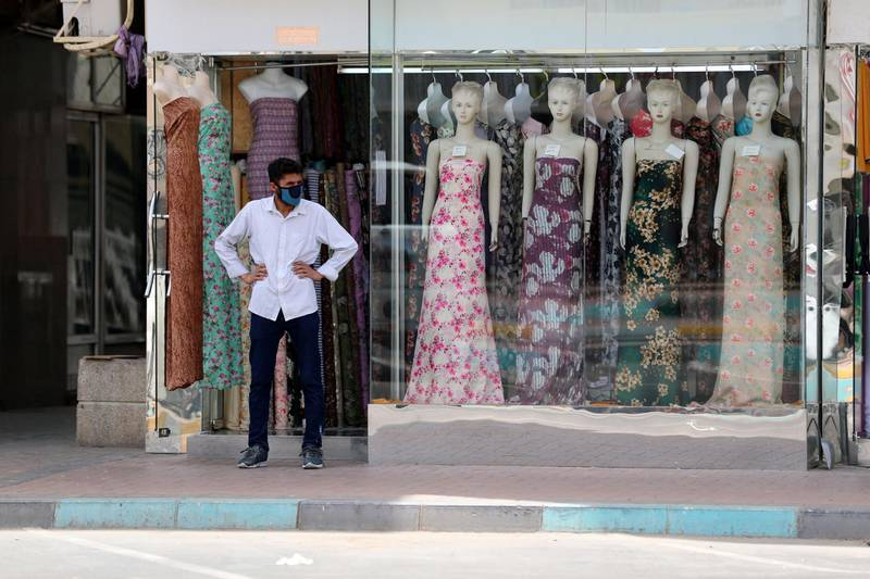 Al Ain, United Arab Emirates - Reporter: N/A: A shopkeeper wearing a facemask waits outside his dress store in Al Ain. Thursday, April 9th, 2020. Al Ain. Chris Whiteoak / The National