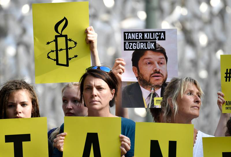 Activists of Amnesty International stage a protest against the detention of the head of Amnesty International in Turkey, Taner Kilic, in front of the Turkish Embassy in Berlin on June 15, 2017. Taner Kilic was arrested in the Turkish province of Izmir along with 22 other lawyers on June 6, 2017 and has been charged with membership of a terrorist organisation and remanded in custody pending trial  / AFP PHOTO / John MACDOUGALL