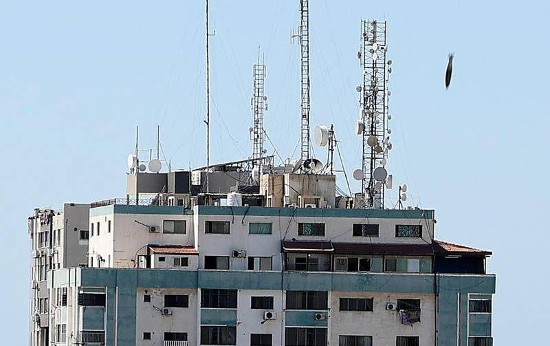 TOPSHOT - An air bomb hits the Jala Tower during an Israeli airstrike in Gaza city controlled by the Palestinian Hamas movement, on May 15, 2021. Israeli air strikes pounded the Gaza Strip, killing 10 members of an extended family and demolishing a key media building, while Palestinian militants launched rockets in return amid violence in the West Bank. Israel's air force targeted the 13-floor Jala Tower housing Qatar-based Al-Jazeera television and the Associated Press news agency. / AFP / Mahmud Hams