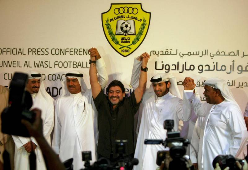 Argentine football legend Diego Maradona (C) gestures with officials of the United Arab Emirates al-Wasel football club following a press conference in Dubai, June 04, 2011. Maradona was introduced as the new coach of the al-Wasel club for the next two years.       AFP PHOTO/MARWAN NAAMANI (Photo by MARWAN NAAMANI / AFP)