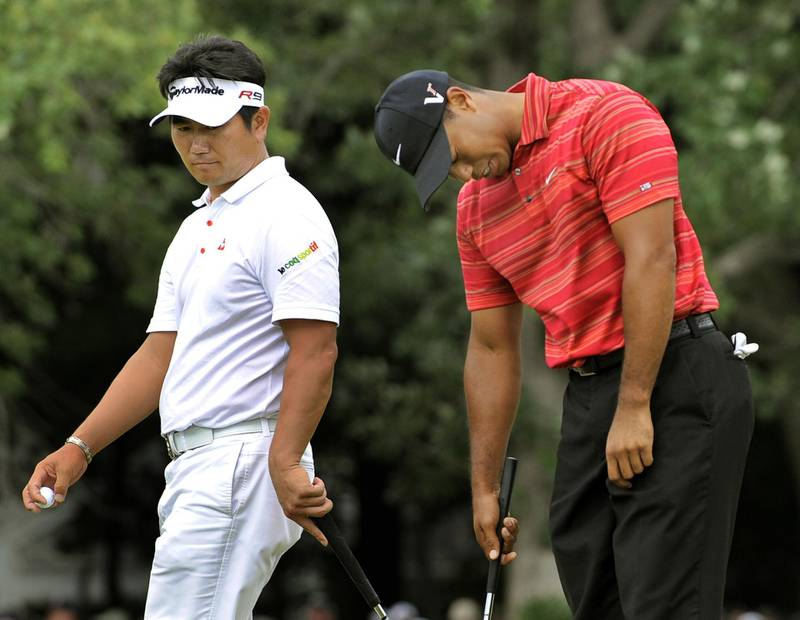 Y.E. Yang of South Korea (L) walks past as Tiger Woods of the US hangs his head after missing his putt on the 13th hole August 16 ,2009 at the 91st PGA Championship at the Hazeltine National Golf Club in Chaska, Minnesota.  AFP PHOTO / TIMOTHY A. CLARY (Photo by TIMOTHY A. CLARY / AFP)