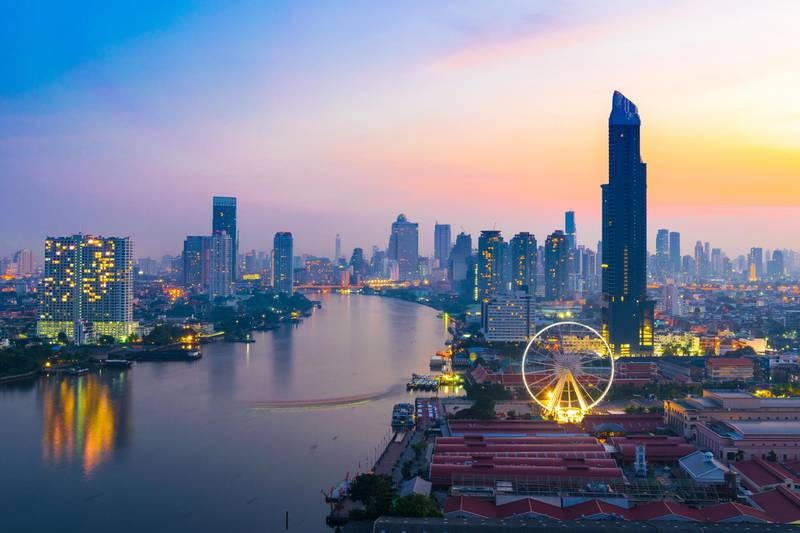 Bangkok city during twilight time, travel and shopping place, Chaophraya River, Condominiums & Hotels, Landmark wheel. Getty Images
