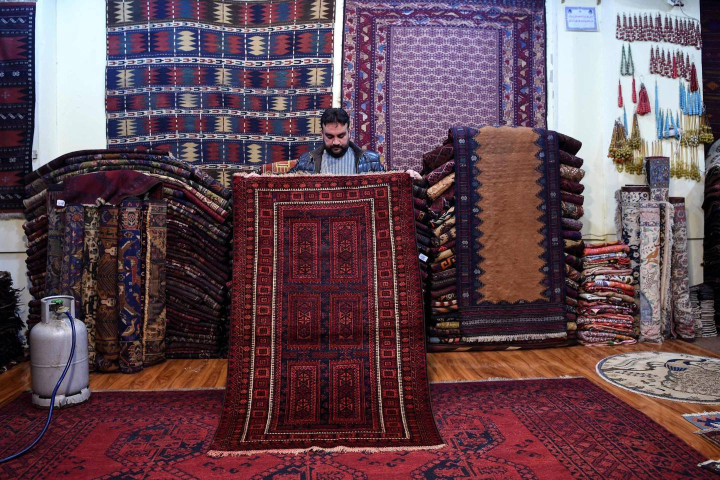 In this picture taken on January 18, 2021, Abdul Wahab, a tribal carpet collector displays a rug during an interview with AFP inside his shop at Chicken Street in Kabul. Rug hunters can spend weeks -- if not months -- passing through villages like sleuths along old caravan trails, offering cash or bartering with modern goods to amass a diverse selection of pieces they can later peddle in rug bazaars or to collectors. - TO GO WITH AFGHANISTAN-RUGS-CONFLICT,FEATURE BY DAVID STOUT  / AFP / WAKIL KOHSAR / TO GO WITH AFGHANISTAN-RUGS-CONFLICT,FEATURE BY DAVID STOUT