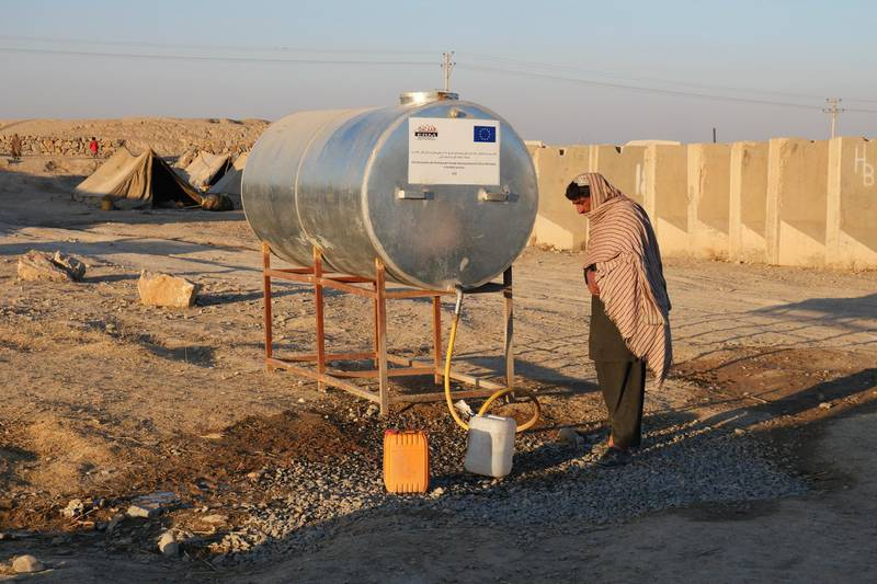 Pictured: A man fills up containers with water at the only water tank supplying a camp of 250 families. Before the tank arrived, people were forced to fill up water at a gas station a few metres down the road.  Photo by Charlie Faulkner January 2021