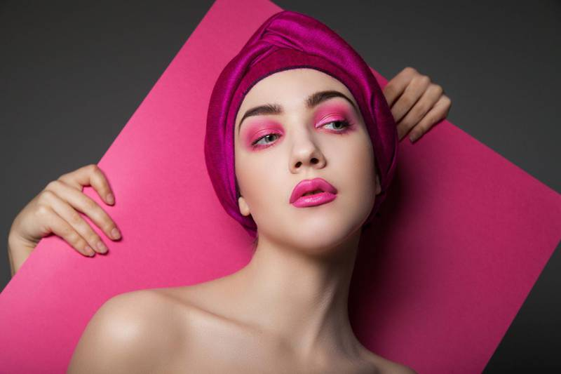 Sensual model wearing pink turban and pink makeup standing against crop hands holding pink paper. Getty Images