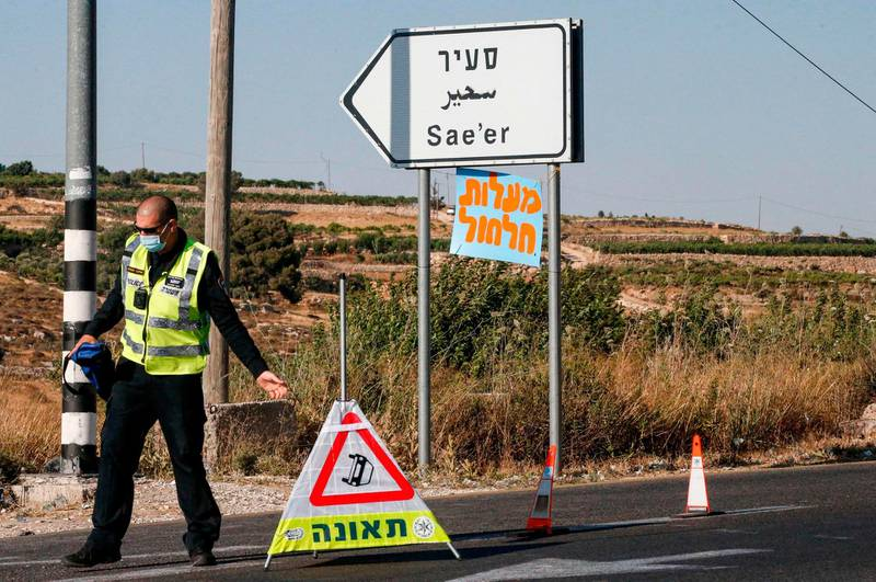 An Israeli policeman prepares to block the entrance to a junction by the Palestinian village of Halhul, north of Hebron in the occupied West Bank, on June 30, 2020, as Israeli settlers arrive to attend a rally against US President Donald Trump's peace plan which might create a Palestinian state and also the Israeli annexation of some parts West Bank.  / AFP / HAZEM BADER