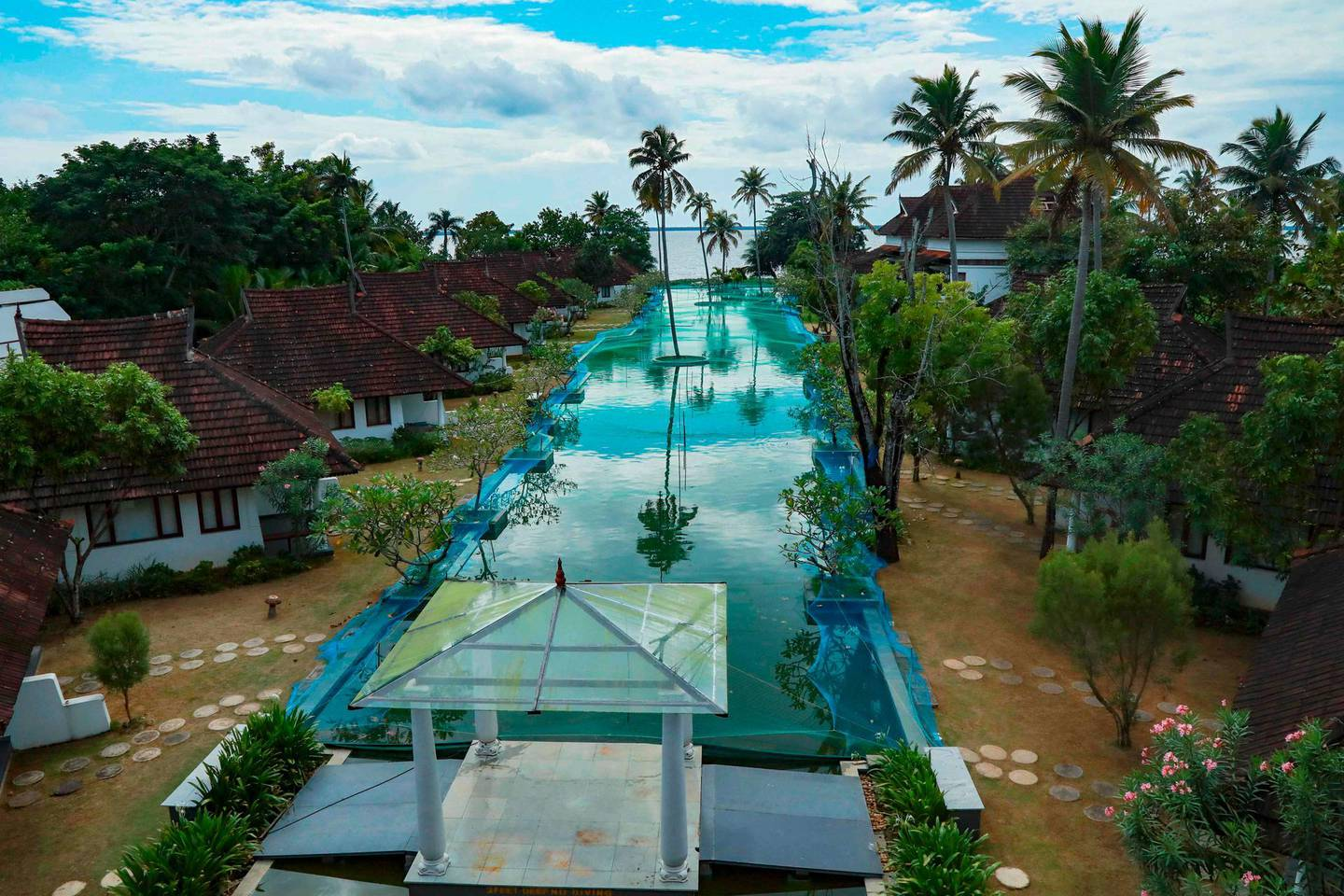 In this picture taken on August 23, 2020, a general view of a swimming pool that has been turned into a fish farm is pictured at Aveda Resort in Kumarakom, in Kerala state. A luxury resort in southern India has turned its swimming pool into a fish farm to stop the business sinking amid the pandemic economic crisis. Normally the 150 metre (500 feet) long swimming pool at the Aveda Resort in Kerala state is packed with European tourists. Now thousands of pearl spot fish are causing the splash. / AFP / Arun CHANDRABOSE