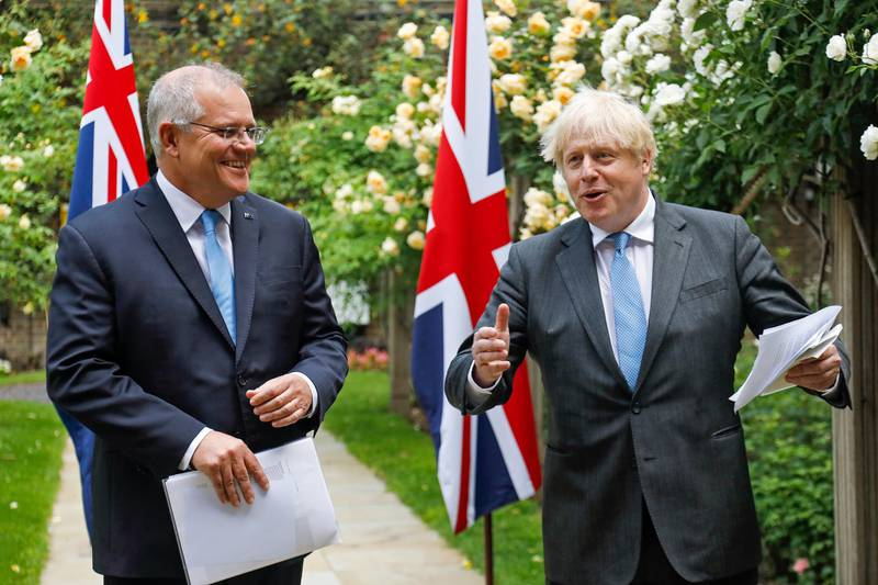 epa09272576 British Prime Minister Boris Johnson (R) and Australian Prime Minister Scott Morrison (L) give a joint news conference during their bilateral meeting in the garden of number 10 Downing Street in London, Britain, 15 June 2021. Britain is set to announce the broad terms of a free-trade deal with Australia on the day, its latest post-Brexit accord as Prime Minister Boris Johnson seeks to expand commerce beyond the European Union (EU).  EPA/LUKE MACGREGOR / POOL