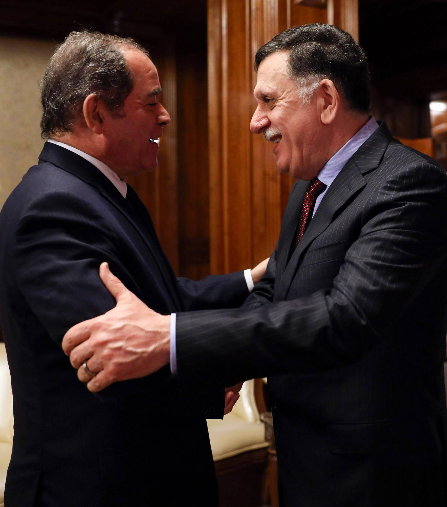Prime Minister of Libya's UN-recognised Government of National Accord (GNA) Fayez al-Sarraj (R) greets Algeria's Foreign Minister Sabri Boukadoum in the Libyan capital Tripoli on February 18, 2020. / AFP / -