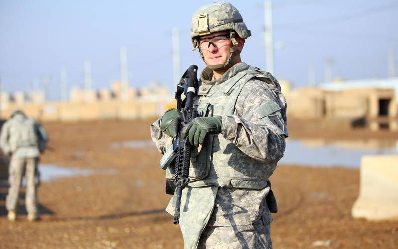 """(FILES) In this file photo a US soldier stands at the Taji base complex which hosts Iraqi and US troops and is located thirty kilometres north of the capital Baghdad on December 29, 2014. Washington warned on October 1, 2020 that it would not tolerate attacks on US interests in Iraq by Iran-backed militias, as Baghdad worries about a possible US withdrawal. """"We can't tolerate the threats to our people, our men and women serving abroad,"""" David Schenker, assistant secretary of state, for near Eastern affairs, told reporters.  / AFP / ALI AL-SAADI"""
