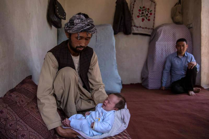 Ahmed Reza, 34, holds his son Abbas at his home in the western outskirts of Kabul, a place of relative calm and safety. His wife Rokaia has been brutally killed in the attack on the maternity ward in Dasht-e-Barchi.