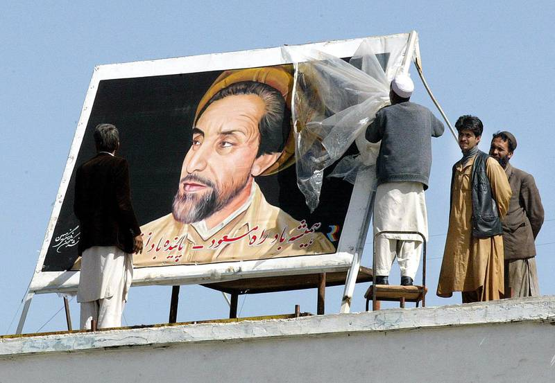 Workers put up a poster of former anti-Taliban commander Ahmad Shah Masood on the building of Kabul International Airport, 03 April 2002.  In homes, in the streets, on car windscreens and even woven into traditional carpets, Masood's chiselled and bearded features keep a watchful eye.     AFP PHOTO/Rosland RAHMAN (Photo by ROSLAN RAHMAN / AFP)