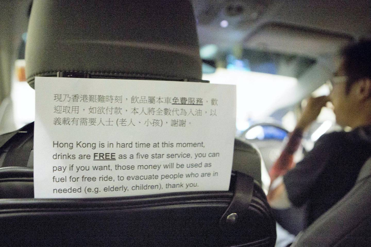 HONG KONG. SCHOOL BUS FEATURE: A sign in the back of an Uber driver's car shows that any donations and money given will go to helping fund his role in being part of the 'school bus' system. 'School Buses', are the collective name to a group of volunteers, including Chen, who offer free transport for people who need help getting away from the protests safely.