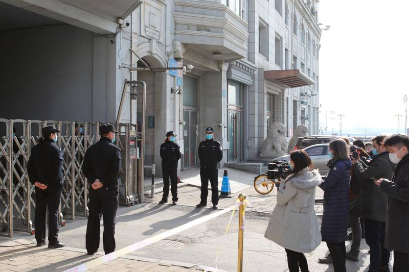 Journalists film as security officers stand guard at an entrance to a court building in Dandong in northeastern China's Liaoning Province, Friday, March 19, 2021. China was expected to open the first trial Friday for Michael Spavor, one of two Canadians who have been held for more than two years in apparent retaliation for Canada's arrest of a senior Chinese telecom executive. (AP Photo/Ken Moritsugu)