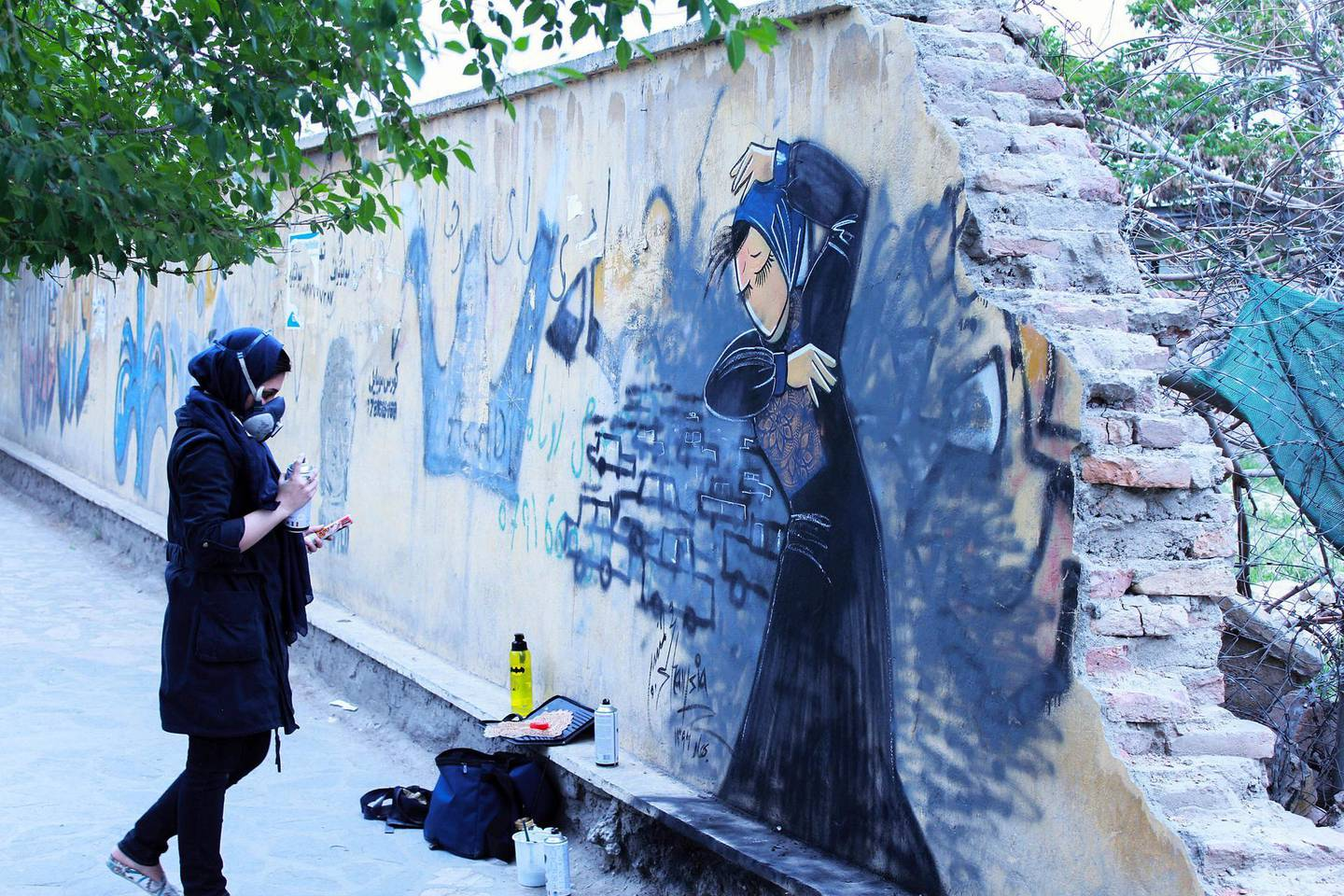 Shamsia Hassani working on one of her pieces on a Kabul wall. To minimise her time outdoors on the unsafe streets of Afghanistan she uses less details and colours. Picture courtesy of Shamsia Hassani