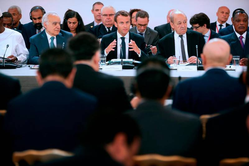 TOPSHOT - French President Emmanuel Macron, flanked by French Minister of Europe and Foreign Affairs Jean-Yves Le Drian (2R) and UN Special Envoy for Libya, Lebanese Ghassan Salame (L) speaks during an International conference on Libya at the Elysee Palace in Paris, on May 29, 2018. Rival Libyan leaders vying for influence in the fractured and war-scarred country meet in Paris for a major peace conference seen as a risky French-backed push for a political settlement in the country. / AFP / POOL / Etienne LAURENT